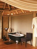 Colonial-style holiday accommodation; bubble bath in antique bathtub with silver claw feet