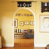 Blick durch Türbogen auf Holzbank mit bunte Decken und Stoffe