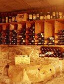 Ausschnitt eines privaten Weinkellers mit Steinwand und Holzregalen