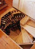 Blick durch offene Bodenlucke auf Weldeltreppe und Weinflaschen entlang der Wand