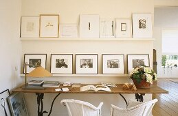 A shelf with pictures above a wall table