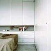 Eine Ecke eines Schlafzimmers mit weißem Einbauschrank und durchlaufender Wandnische als Ablagefläche