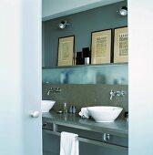 Ein Badezimmer in Grautönen mit Milchglaswänden und modernem Waschtisch