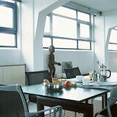 Frühstücksgedeck auf einem eleganten, schwarzen Tisch in einem Loft mit Rippendecke