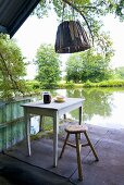 Table and chair on the verandah of a boathouse