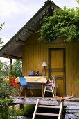 Wooden summer house with table and chairs on verandah