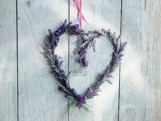 Heart-shaped lavender wreath hanging on a wooden wall