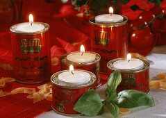 Tea lights in tins with basil and pasta as table decoration