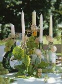 Weinflaschen mit Weinblättern dekoriert als Kerzenhalter