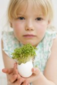 Little girl holding eggshell with cress growing in it