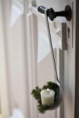 Candle and white spruce twigs in enamel ladle on door handle