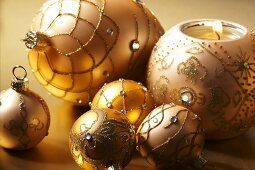 Champagne coloured Christmas baubles and a ball shaped candle holder