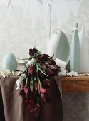 Vases and a bouquet of purple zantedeschia and tulips in front of torn wallpaper