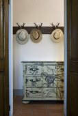 Open doorway with a view to hats on wall hooks and painted chest of drawers