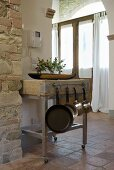 Trolley out of stainless steel and large wooden tray in the lfoyer of a mediterranean country home