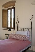 Iron bedstead with pink bed linen and bolster next to a window