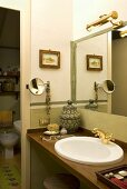 Corner of a bathroom with washstand and brass fittings in front of a mirror and open door with a view into a toilet
