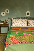 Bed with a printed bedspread and framed mirrors on a wall