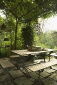 Table and benches under a pergola covered in greenery