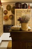 Basket with dried flowers and pillows on a rustic chest of drawers and collection of hats on a wall