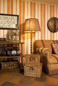 Two piece basket set in front of a floor lamp next to a sofa and wallpaper with an orange and white striped pattern