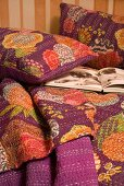 Bedspread and pillows covered in the same colorful fabric