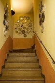 Staircase with wooden steps and collection of mirrors on a yellow wall