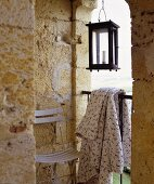 A chair, summer blanket and a lantern on a terrace