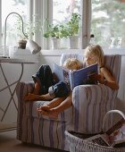 Two children sitting in an armchair reading a book