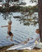 A boy jumping into a lake and his mother leaning against a tree
