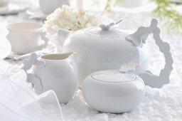 Weisse Teekanne mit Zuckerdose und Milchkännchen auf weisser Tischdecke