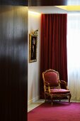 A baroque armchair with a red upholstery in front of a velvet curtain in the corner of a room