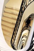 Looking down on a stairway with black banisters in a manor house