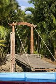 A wooden drawbridge at the edge of the jungle