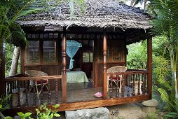 A veranda with a wooden balustrade and a thatched roof with a view into a bedroom