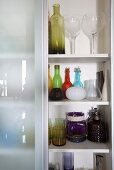 A cupboard filled with coloured glass bottles (cropped)