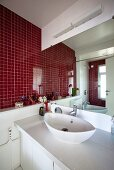 A red-tiled wall in a bathroom with a view of the basin