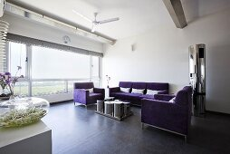 A purple three-piece suite in front of a large window