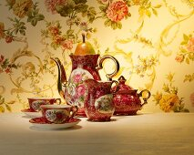 Tea cups and a tea pot with a pear as a lid