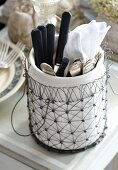 Cutlery in a porcelain pot in a metal basket
