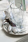 Glasses and silver cutlery on a plate