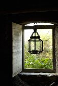 Lantern in a open window hanging on a lintel with wooden shutters on the inside and a view onto a garden