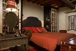 Bed with upholstered headboard and red bed linen in a bedroom in a country home