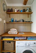 Niche with wood consoles with bathroom items in front of wall of brown tiles