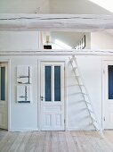White attic room with a view through a wooden beams into the gallery