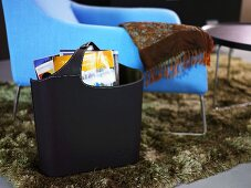 Black bag with magazine in front of a blue chair