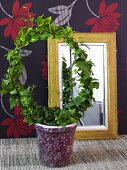 Wreath shaped plant in a pot and mirror in front of black wallpaper with a floral pattern