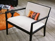 Upholstered armchair with black wooden frame on a rustic wood plank floor