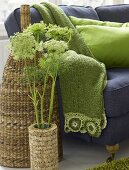 A cork plant pot in front of a rattan vase and green blanket on a sofa