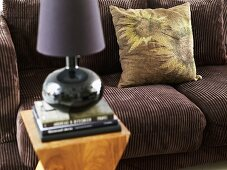 Brown corduroy sofa with pillows and side table with table lamp